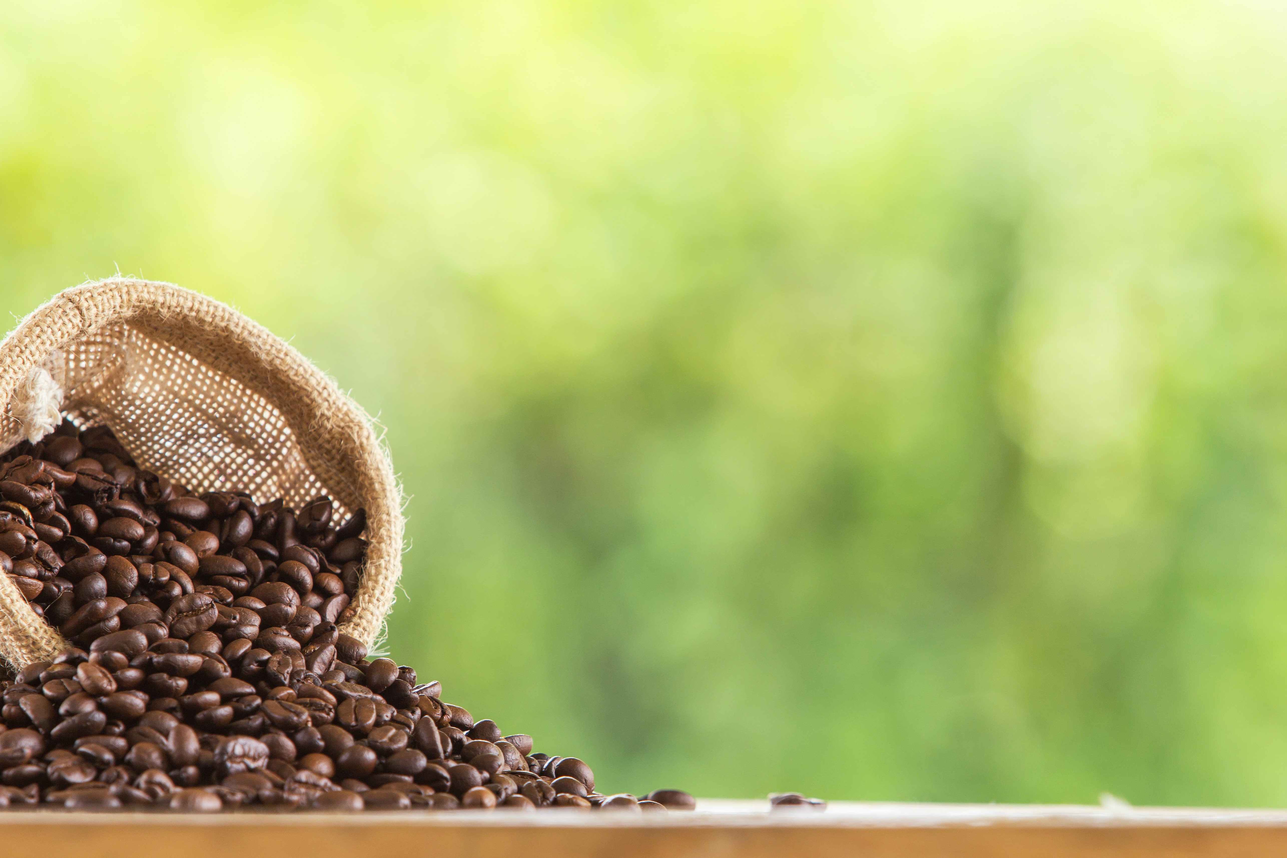 coffee-bean-sack-wooden-tabletop-against-grunge-green-blur-background-min